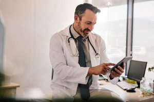 physician on phone using WELL Health